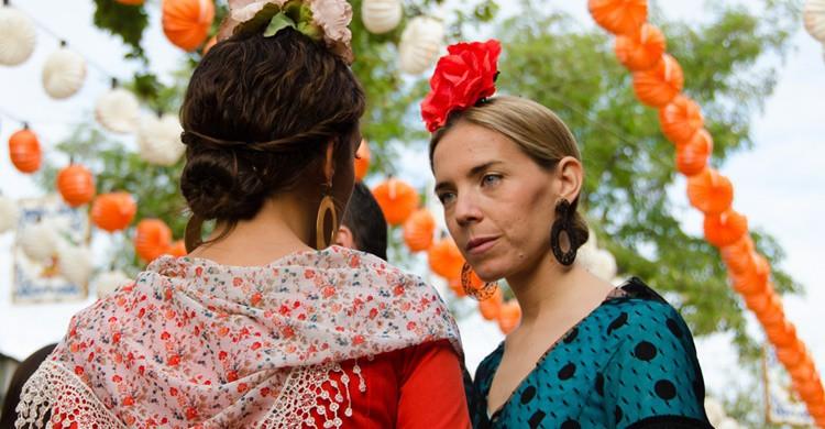 Dos mujeres vestidas de sevillanas charlan en la Feria. Sandra Vallaure (Flickr)