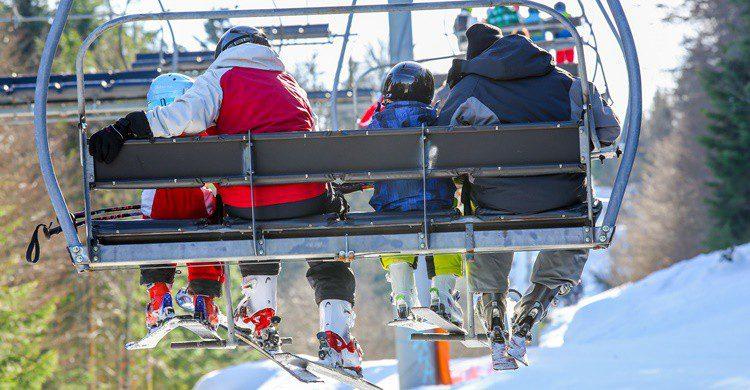 Familia en telesilla en la nieve. Pixinoo (iStock)