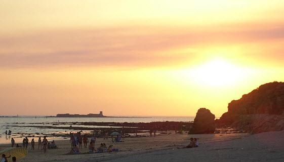 Atardecer en la playa de la Barrosa, con el islote y castillo de Sancti Petri al fondo. Foto de Peejayem