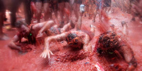 """Jóvenes disfrutan de la fiesta, mientras """"nadan"""" en un río de tomates."""
