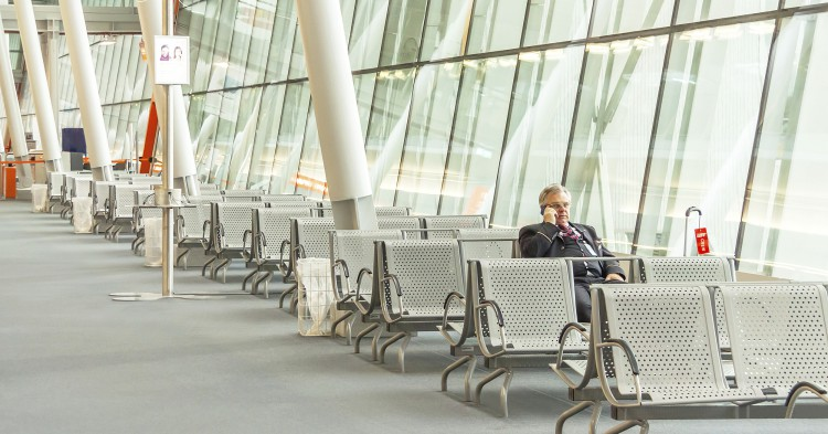 Airport business man with smart phone is waiting in terminal for