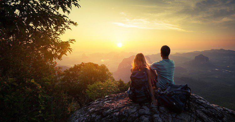 Pareja viendo una puesta de sol en la naturaleza. Mihtiander (iStock)