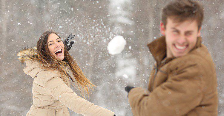 Pareja jugando en la nieve. AntonioGuillem (iStock)