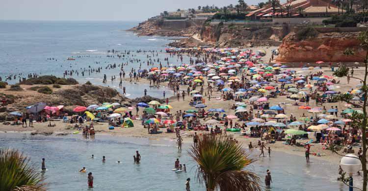 playa llena de bajistas y turistas