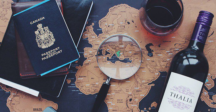Un mapa, un pasaporte, una botella de vino y una lupa