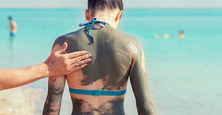 Una mujer se aplica barro en el Mar Muerto