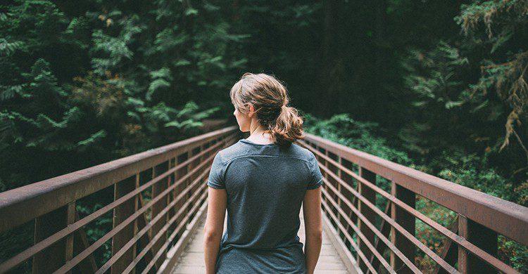 Una mujer en un puente en plena naturaleza