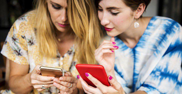 Dos chicas miran sus celulares
